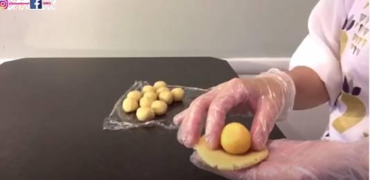 把月餅皮壓平,包入奶黃餡料,收口且滾圓。(圖片來源:甜師奶)